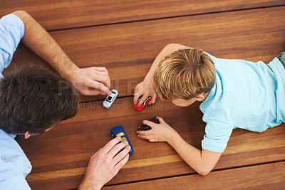 Buy stock photo Overhead view of a father and his son playing with toy cars on the floor