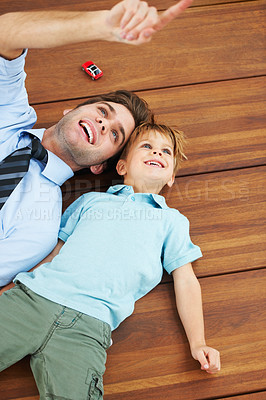 Buy stock photo A cute boy and his young father lying on the floor and looking up at something
