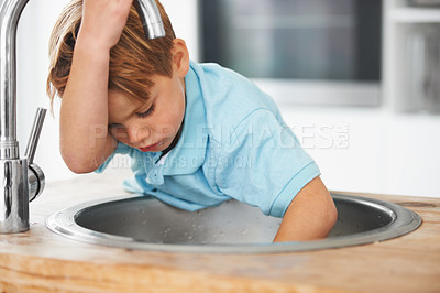 Buy stock photo A cute young boy busy with something in the kitchen sink