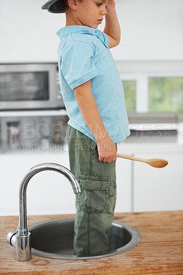 Buy stock photo Cropped image of a cute young boy standing in the sink with something on his head and a wooden spoon in his hand