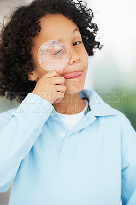 Buy stock photo Portrait of a cute young boy looking while holding a magnifying glass over his closed eye