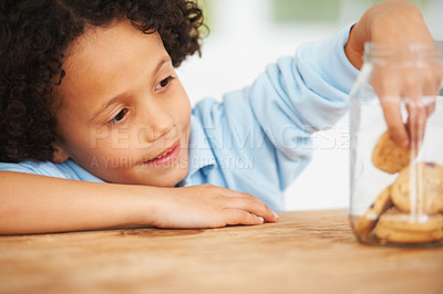 Buy stock photo A cute young boy grabbing a cookie from the cookie jar