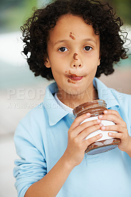 Buy stock photo A little boy eating Nutella from a jar