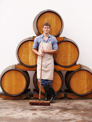 Buy stock photo A young wine maker standing in front of some wine barrels while holding a broom