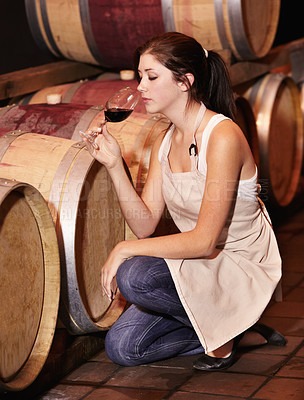Buy stock photo A young wine maker testing her red wine straight from the barrel