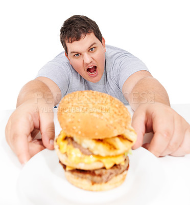 Buy stock photo An obese young man reaching out to grab a huge hamburger and looking ravenous