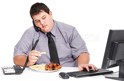 Buy stock photo Shot of an obese young office work sitting at his workstation eating
