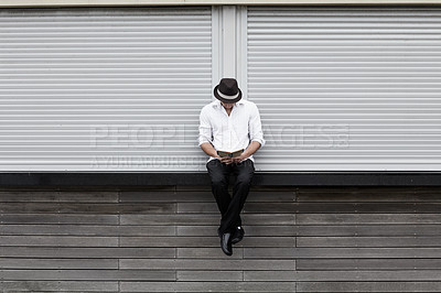 Buy stock photo A formally dressed man sitting on a ledge and reading