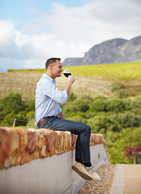 Buy stock photo A mature man sitting on wall and enjoying a glass of red wine