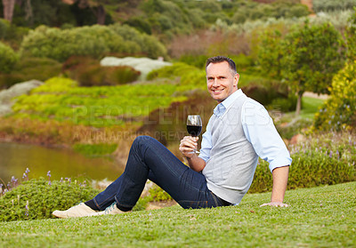 Buy stock photo A mature wine maker sitting outside while enjoying a glass of red wine