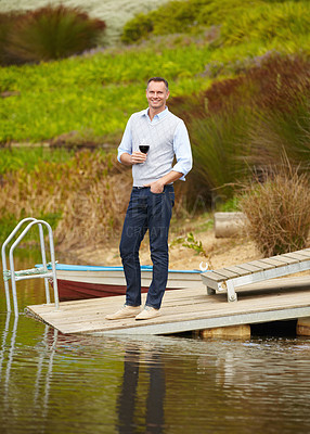 Buy stock photo Portrait of a mature man standing on a jetty with a glass of red wine