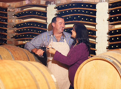 Buy stock photo A mature wine maker toasting with his wife while in his wine cellar