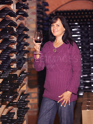 Buy stock photo Portrait of a mature woman with a glass of wine in a wine cellar