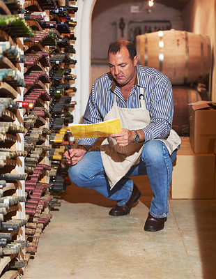 Buy stock photo A mature man doing a wine stock take in his cellar