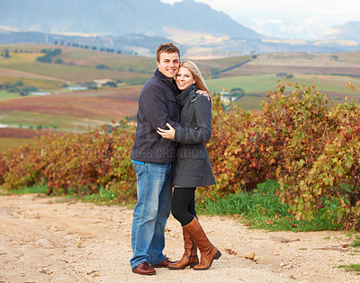 Buy stock photo Portrait of a young couple standing together in the vineyards