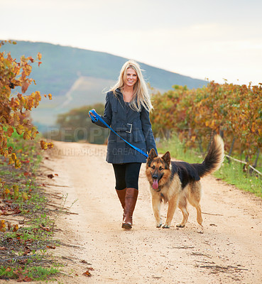 Buy stock photo Portrait of a pretty young woman walking her Alsatian in a vineyard