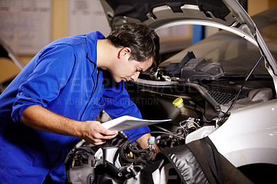 Buy stock photo A male mechanic holding some papers while working on the motor of a car