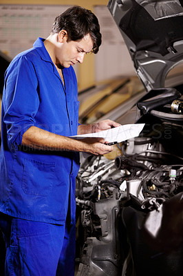 Buy stock photo A male mechanic looking at some papers while working on the engine of a car