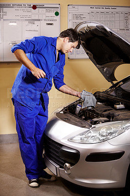 Buy stock photo A male mechanic wiping off the oil stick to measure a car's oil