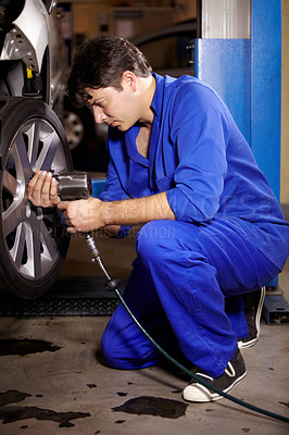 Buy stock photo A male mechanic working on the wheel of a car