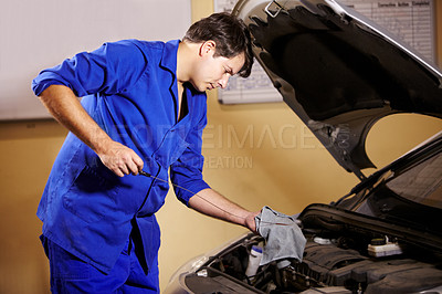 Buy stock photo A male mechanic wiping off the oil stick before measuring a car's oil