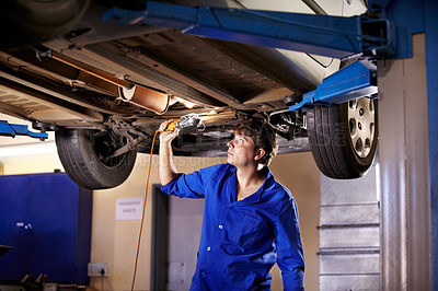 Buy stock photo A young male mechanic using a light to look underneath a car