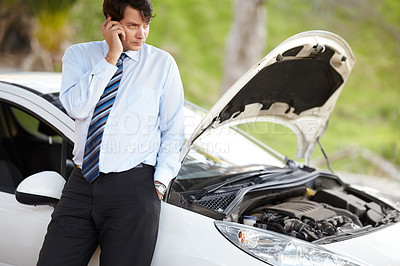 Buy stock photo A man phoning roadside assistance for his broken down car