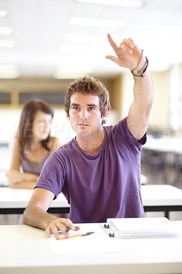 Buy stock photo A young caucasian man raising his hand in class to ask a question
