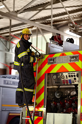 Buy stock photo A young male firefighter on the ladder at the back of a firetruck