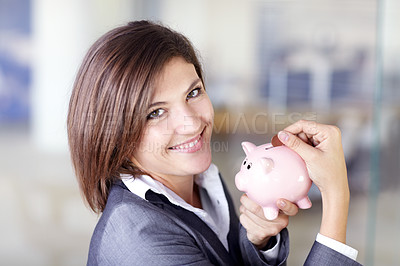 Buy stock photo Portrait of an attractive businesswoman putting a coin into a piggybank