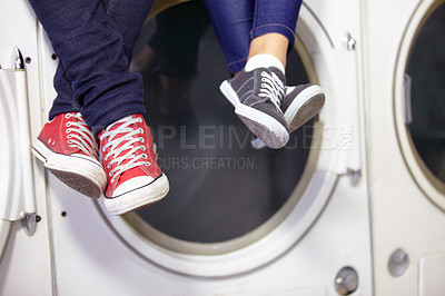 Buy stock photo Cropped image of a couple's feet as they sit on a washing machine at the laundromat