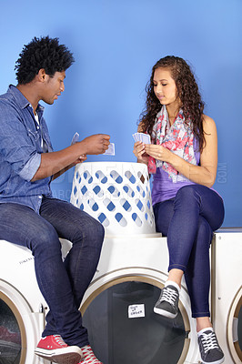 Buy stock photo A young ethnic couple sitting on a washing machine at the laundry and playing cards