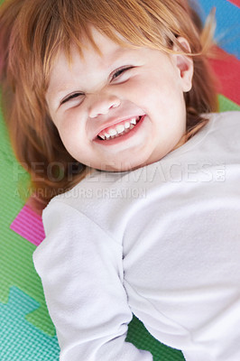 Buy stock photo Shot of a little girl lying on her back and laughing