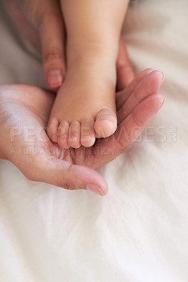 Buy stock photo Cropped image of a mother's hands holding her baby boy's foot
