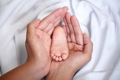 Buy stock photo Closeup of a mother's hands holding her baby girl's foot