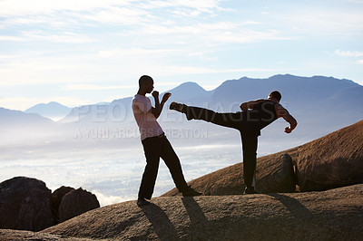 Buy stock photo Two male kickboxers training on a mountain top
