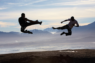 Buy stock photo Two male kickboxers fly kicking one another on top of a mountain