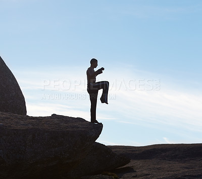 Buy stock photo A male kickboxer balancing on a cliff