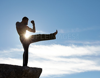 Buy stock photo A male kickboxer training on a cliff with the sun shining on him