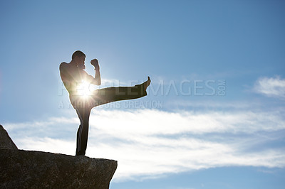 Buy stock photo A male kickboxer practising on a cliff with the sun shining on him