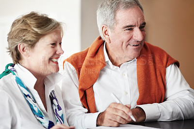 Buy stock photo A senior couple filling out forms at their hotel reception desk