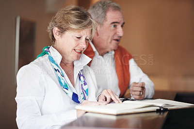 Buy stock photo A senior couple filling out forms at the hotel reception desk
