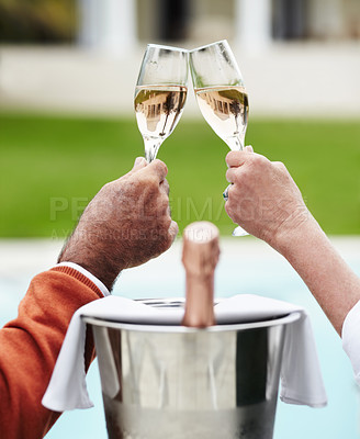 Buy stock photo Closeup of a senior couple clinking their champagne glasses together while on vacation