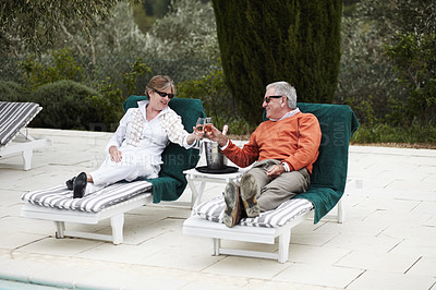 Buy stock photo A senior couple toasting to their vacation at the hotel pool