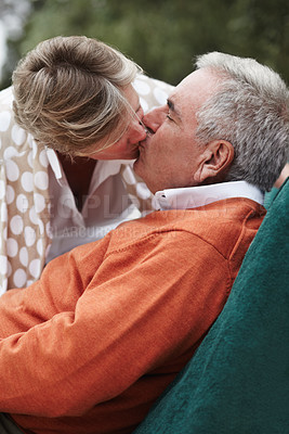 Buy stock photo A delighted senior man getting a kiss from his wife while on a relaxing vacation