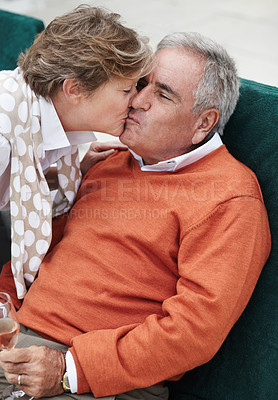 Buy stock photo A delighted senior man getting a kiss from his wife while enjoying champagne on vacation