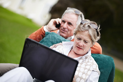 Buy stock photo A senior couple using a laptop while on vacation