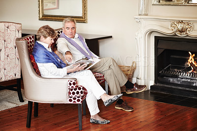 Buy stock photo A senior couple relaxing by the fire while on vacation