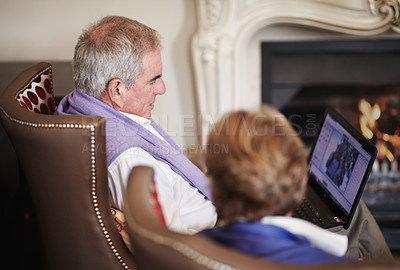 Buy stock photo A senior couple looking at photos taken during the day while on a vacation