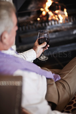 Buy stock photo A senior man relaxing by the fire with a glass of red wine